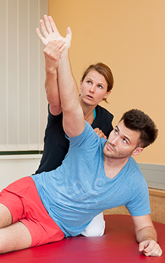 Therapeutin mit Patient bei der Physiotherapie